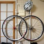 ロードバイクのホイールとヘルメットをラックに吊るした写真